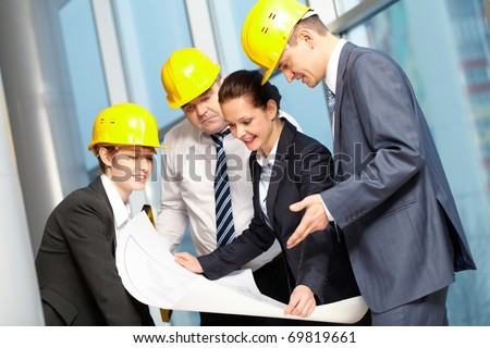 Four confident engineers discussing a plan - stock photo