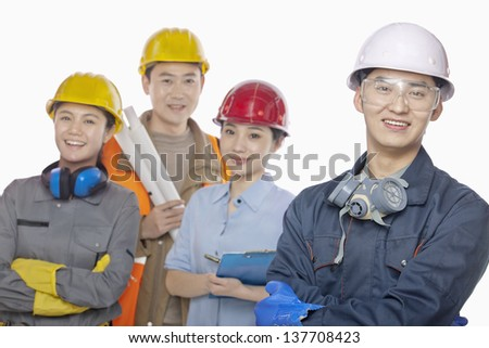 Four construction workers against white background, focus in foreground - stock photo