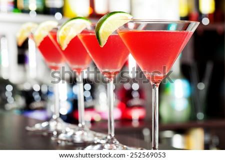 Four cosmopolitan cocktails on a bar - stock photo