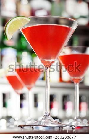 Four Cosmopolitan cocktails on a bar, soft focus - stock photo