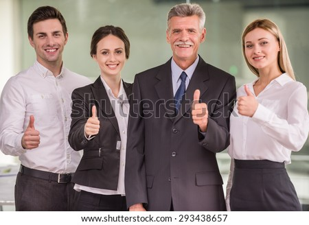 Four coworkers dressed formal standing at modern office and looking at camera. - stock photo