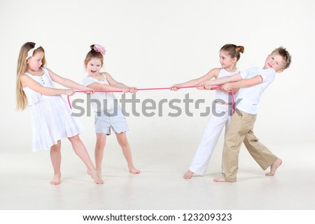 Four cute little boys and girls in white clothes overtighten pink rope. - stock photo