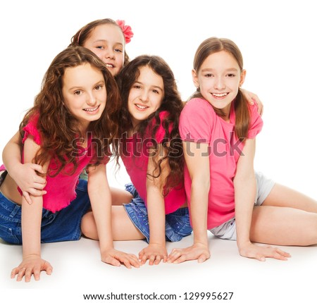 Four cute 10 years old girls in pink sitting and hugging on the floor, smiling and look happy, isolated on white - stock photo