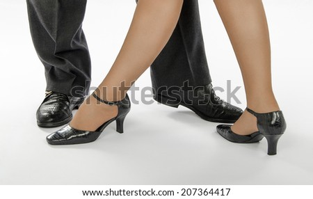 Four dancing legs standing in tango pose on white background - stock photo