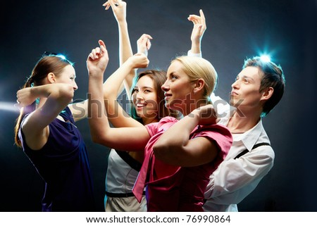 Four dancing people isolated on black - stock photo