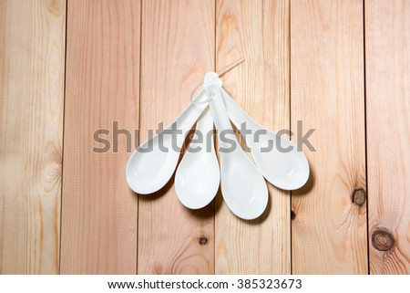 Four decorate white spoon from top view with pain wood background. Selective focus with shallow depth of field. - stock photo