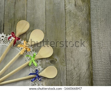 Four decorated wooden spoons on white napkin and wooden background - stock photo