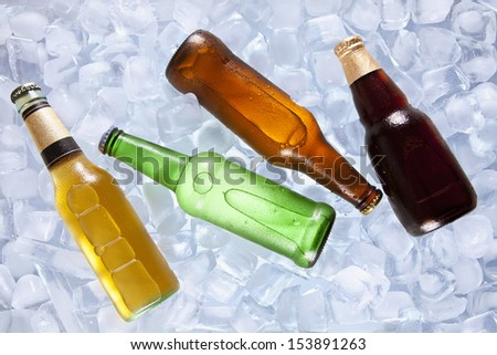 Four different bottles of beer cooling on ice. - stock photo
