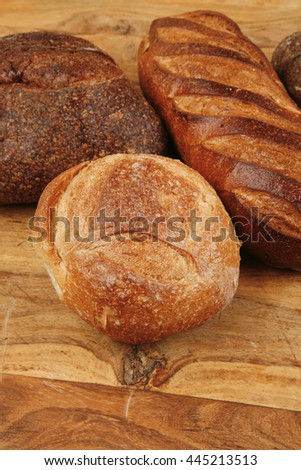 four different rye and white flour fresh french bread loaf on light wooden table - stock photo
