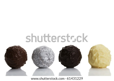 four different truffle pralines in a row on white background - stock photo
