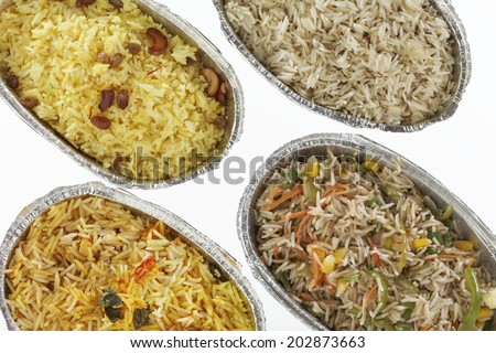 Four different varieties of Indian rice- vegetarian Biryani, Chinese fried rice, Jeera rice & sweet coconut rice in metal foil tray - stock photo
