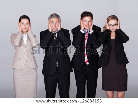 Four diverse businesspeople standing in a row holding their ears in a conceptual representation of the saying - Hear no evil - stock photo