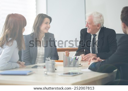 Four elegant businesspeople on company meeting - stock photo