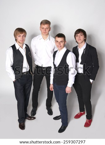 Four elegant young men student standing smiling relaxed in full length over white background. High angle view - stock photo