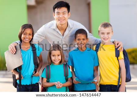 four elementary school students and teacher on campus - stock photo