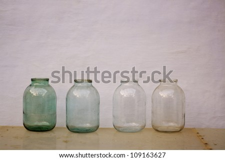 four empty old fashioned glass jars on the table - stock photo