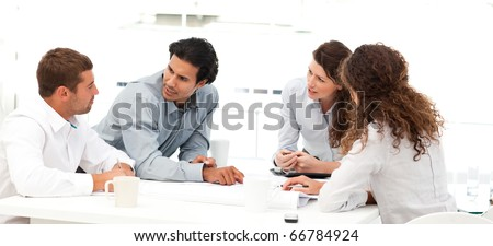 Four engineers discussing about a new project around a table - stock photo