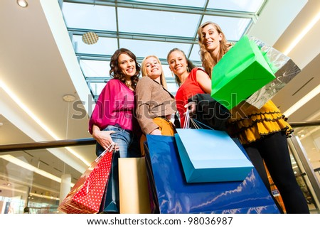 Four female friends with shopping bags having fun while shopping in a mall, stores in the background - stock photo
