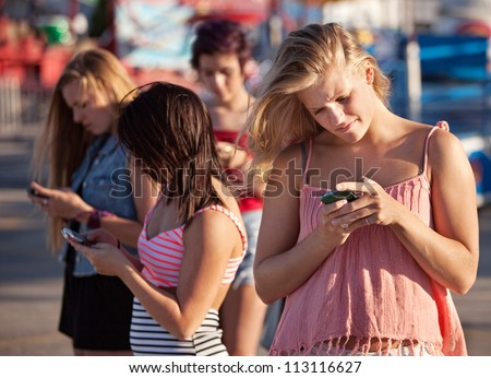 Four female teenagers using their phones outside - stock photo