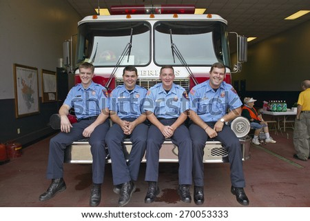 Four firemen sitting on front of fire truck in Americus Georgia - stock photo