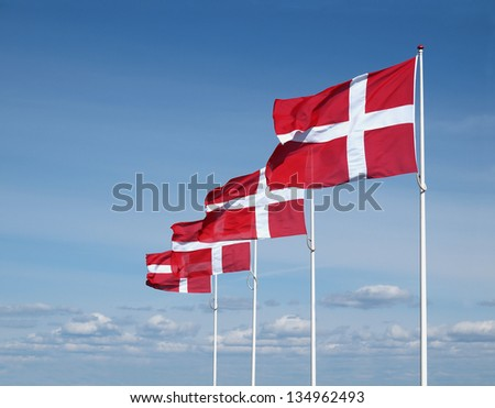 four flapping danish flags on clear blue sky - stock photo