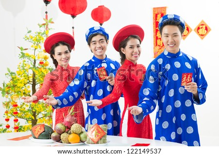 Four friendly Vietnamese inviting to their Tet festive table - stock photo