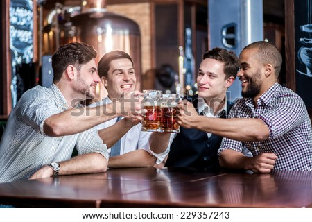 Four friends businessmen drink beer and rejoice together at the bar. Confident business people having fun with friends at the bar with a beer. - stock photo