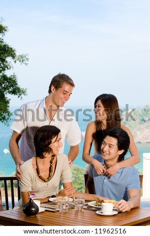 Four friends chatting together at breakfast on vacation - stock photo
