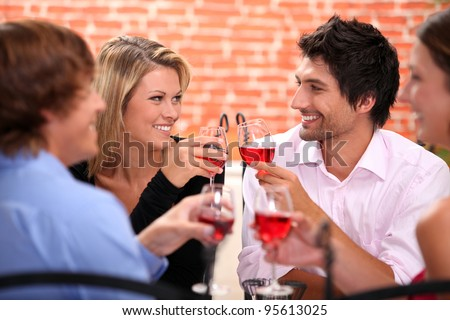 Four friends drinking in restaurant - stock photo