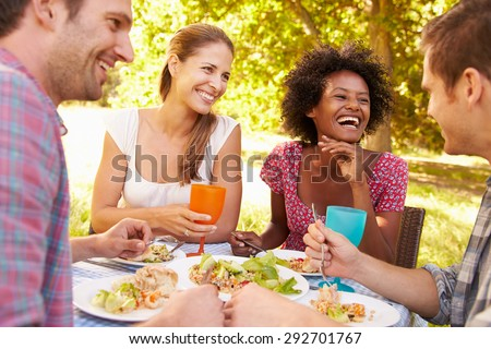Four friends eating together outdoors - stock photo