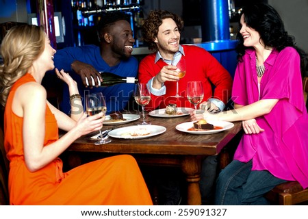 Four friends enjoying drinks at restaurant - stock photo
