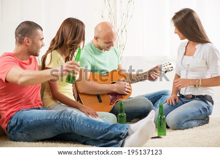 Four friends enjoying with guitar and beer together at the home party. - stock photo