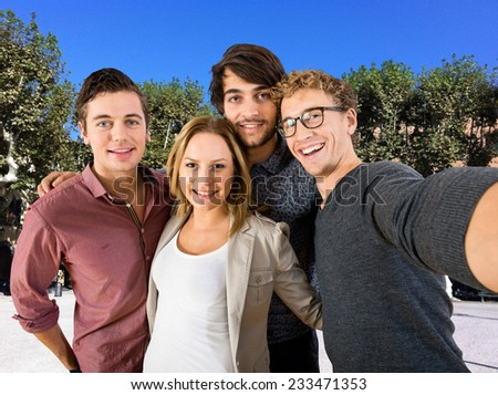 Four friends on vacation taking a selfie on the town square to share on social media platforms - stock photo