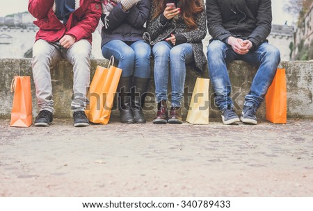 Four friends sitting on a wall and chatting after buying presents - people with shopping bags - stock photo