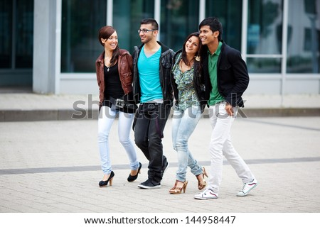 four friends walking together through the city - stock photo