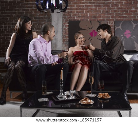 Four Friends With Drinks at Party - stock photo