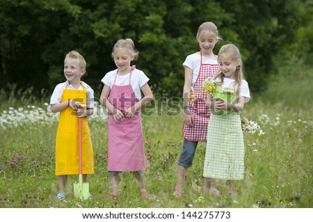 four gardening children with aprons and flowers - stock photo