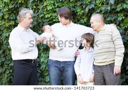 Four generations of men playing with a newborn baby girl - stock photo