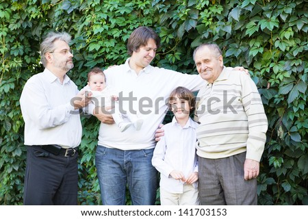 Four generations of men standing in the garden - stock photo