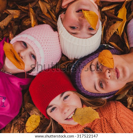 Four girls playing with autumn leaves, lying with closed eyes - stock photo