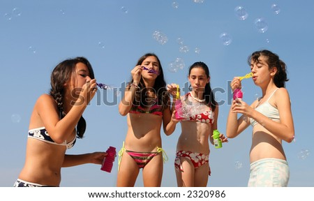 Four girls playing with bubbles on the beach - stock photo