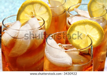 Four glasses of lemon ice tea, outside by the pool. - stock photo