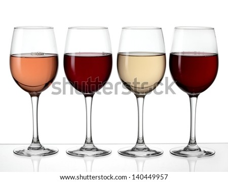 Four glasses with red, rose and white wine - stock photo