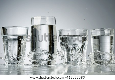 Four Glasses with water and water splash - stock photo