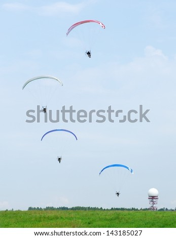 Four gliders in the sky in airport and blue sky background, landing parachutist, skydivers with gliders open landing, paragliding over the forest against blue sky, paragliders flying,Lithuania,sport - stock photo