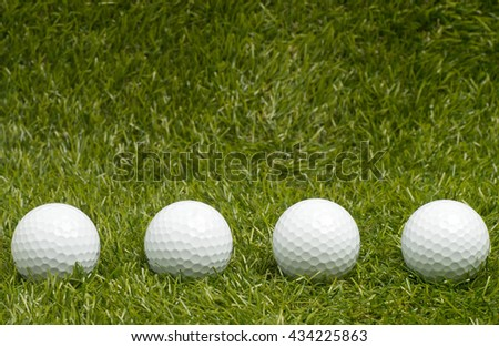 Four golf balls on green grass. - stock photo