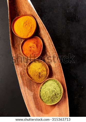 Four ground spices for Asian cuisine in small round bowls in a wooden dish including ginger, chili, turmeric and amchoor or matcha powder, viewed from above on black - stock photo