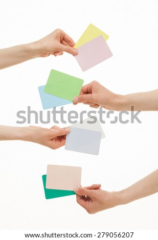 Four hands holding colorful paper cards, white background - stock photo