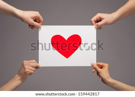 Four hands holding paper with red heart on grey background - stock photo
