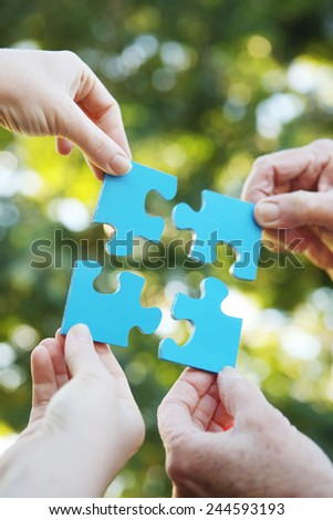 Four hands holding up a jigsaw puzzle - stock photo